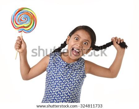 happy female child holding big lollipop candy pulling her pony tail with crazy funny face expression in sugar addiction and kid love for sweet candy concept isolated on white background - stock photo