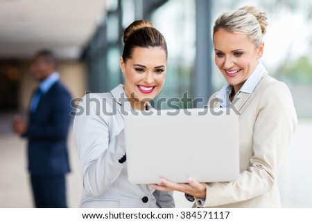 happy female colleagues working on laptop computer in modern office - stock photo