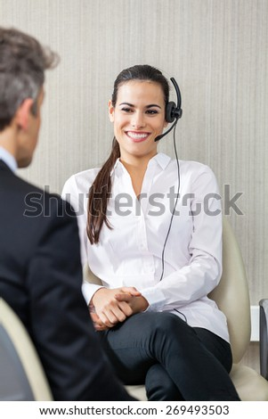 Happy female customer service agent wearing headset while looking at manager in office - stock photo