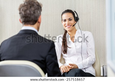 Happy female customer service representative wearing headphones talking to manager in office - stock photo