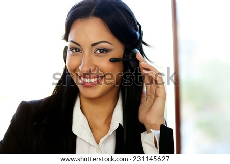 Happy female customer support operator with headset - stock photo