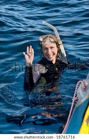 Happy female diver in water next to boat board. Shot in Sodwana Bay, KwaZulu-Natal province, Southern Mozambique area, South Africa. - stock photo