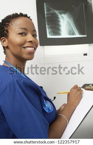 Happy female doctor examining x-ray image in hospital - stock photo