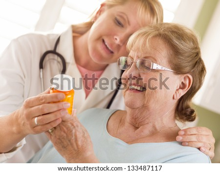 Happy Female Doctor or Nurse Explaining Prescription to Senior Adult Woman. - stock photo
