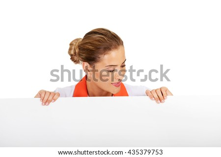 Happy female doctor or nurse holding empty banner - stock photo