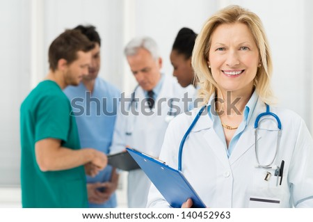 Happy Female Doctor Standing In Front Of Her Co-worker - stock photo