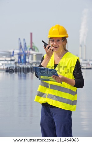 Happy female engineer communicating on a wireless radio, holding a clipboard with notes, wearing a hard hat, safety goggles and a reflective vest for safety - stock photo
