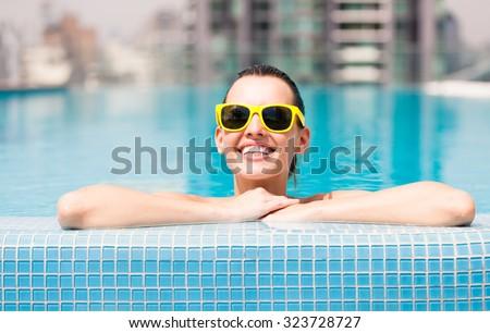 Happy female enjoying the swimming pool.  - stock photo