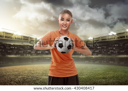 Happy female football fan holding ball on the field - stock photo
