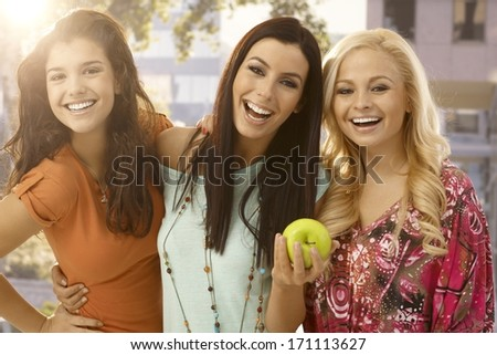 Happy female friends hugging and smiling outdoors, one holding green apple. - stock photo