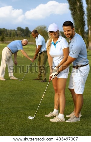 Happy female golfer learning to play. - stock photo