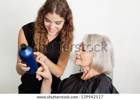 Happy female hairdresser advising hair color to client in parlor - stock photo