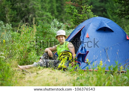 Happy female hiker in front of camp tent against forest - stock photo