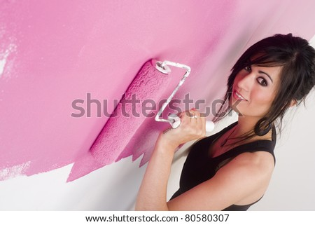 Happy Female Homemaker Applies Pink Paint via Roller Home Improvement Project - stock photo