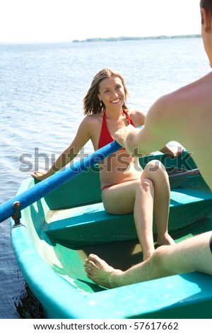 Happy female in bikini sitting in boat and looking at man while floating - stock photo
