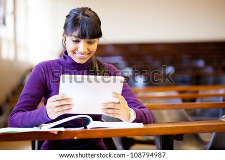 happy female indian college student using tablet computer in classroom - stock photo