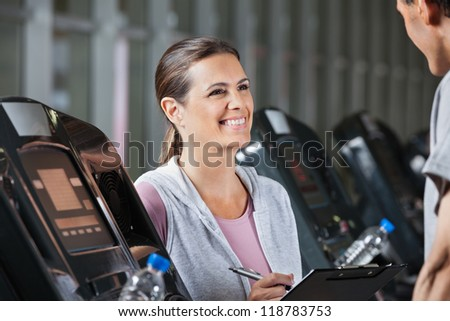 Happy female instructor looking at male client exercising on treadmill in health center - stock photo