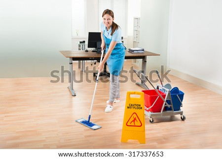 Happy Female Janitor With Cleaning Equipments Cleaning Hardwood Floor In Office - stock photo