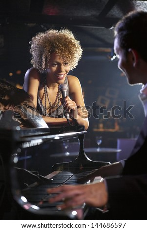 Happy female jazz singer and pianist on stage - stock photo