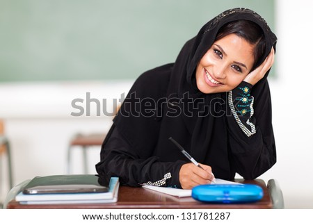 happy female middle eastern high school student sitting in classroom - stock photo