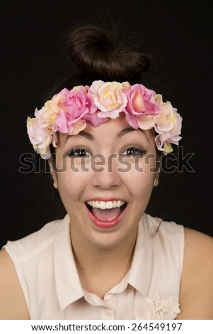 Happy female model wearing floral crown portrait - stock photo