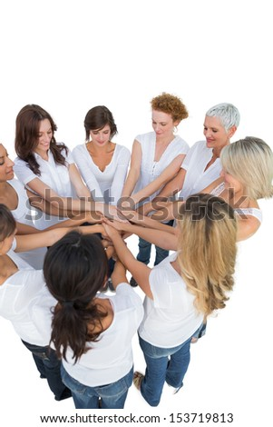 Happy female models joining hands in a circle on white background - stock photo