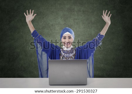 Happy female muslim raised her arms with laptop and blank board - stock photo