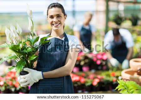 happy female nursery owner with pot of flowers inside greenhouse - stock photo