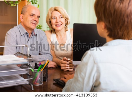 Happy female of pensioners talking with manager at notary's office - stock photo