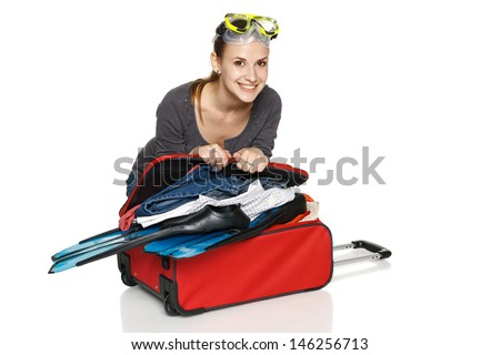 Happy female packing her suitcase for vacations, isolated on white background - stock photo