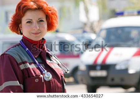 Happy female paramedic standing in front of ambulance machines background outdoors - stock photo