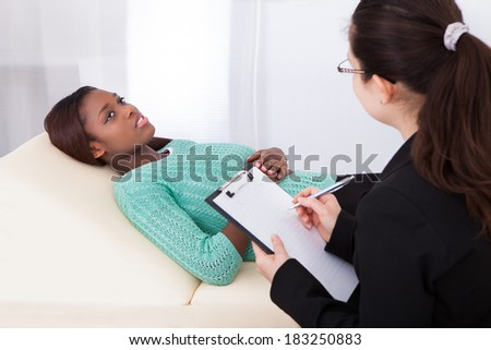 Happy female patient talking to psychologist while lying on bed in clinic - stock photo