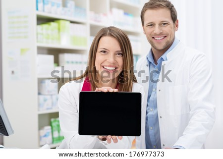 Happy female pharmacist doing a promotion displaying the blank screen of a tablet-pc to the camera as she stands in the pharmacy with a male colleague - stock photo