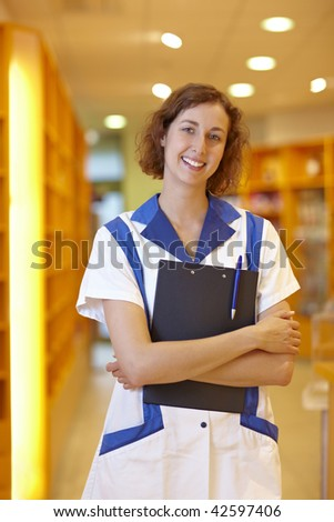 Happy female pharmacist with clipboard in pharmacy - stock photo