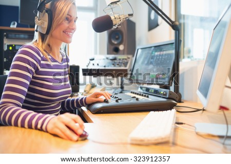 Happy female radio host using computer while broadcasting in studio - stock photo