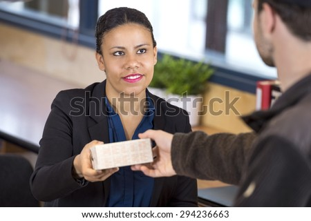 Happy female receptionist receiving parcel from delivery man in office - stock photo