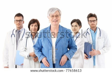 Happy female senior patient standing in front of medical team, smiling, looking at camera, isolated on white.? - stock photo