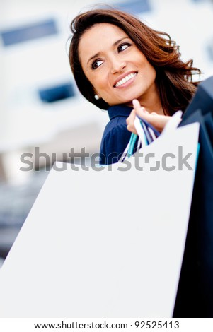 Happy female shopper smiling and carrying bags - stock photo