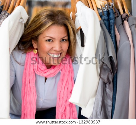 Happy female shopping for clothes at a retail store - stock photo