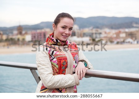 Happy female standing at pier in cold spring day - stock photo