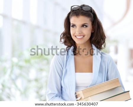 Happy female student on school corridor looking away, smiling. - stock photo