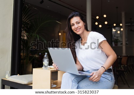 Happy female student posing for the camera while work on net-book and resting after lectures in coffee shop, smiling beautiful latin woman using laptop computer for remote work while sitting in cafe - stock photo