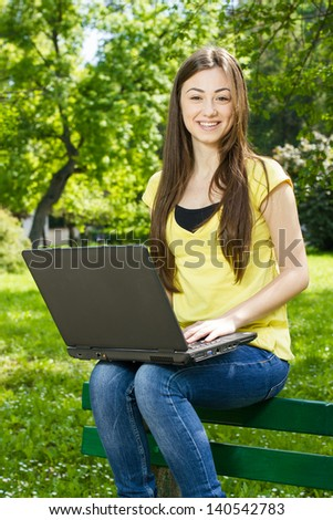 Happy female student using laptop in the park. - stock photo