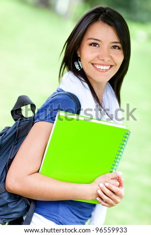 Happy female student with backpack and notebooks smiling - stock photo