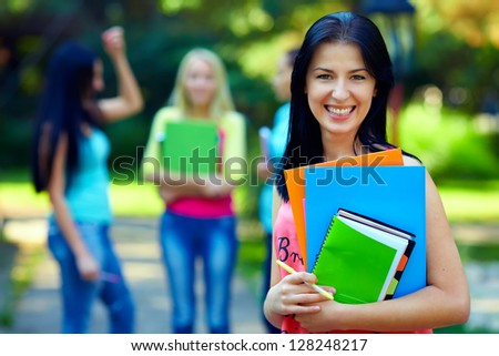 happy female student with colorful books outdoors - stock photo
