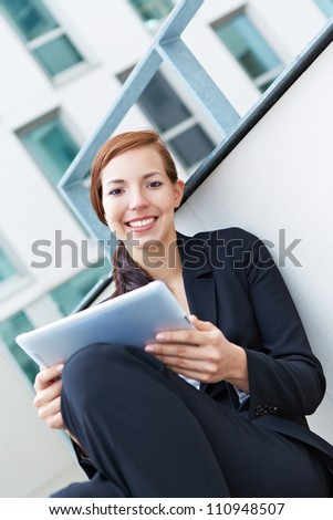 Happy female student working on tablet computer in university - stock photo