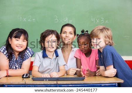 Happy female teacher with her multirace classroom at school desk. - stock photo