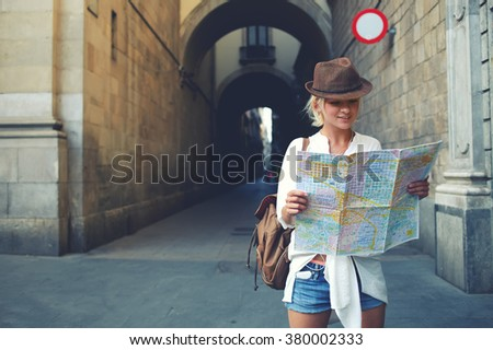 Happy female tourist with backpack on shoulders exploring map while standing in alley near vintage building, trendy woman traveler with smile reading geographical atlas while touring in old city - stock photo