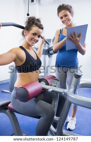 Happy female trainer and client on weights machine in gym - stock photo