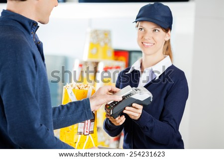 Happy female worker accepting payment through NFC technology from man at concession counter in cinema - stock photo